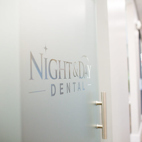 The Night & Day Dental logo on a glass door