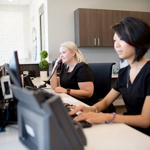 Front desk staff at Night and Day Dental working and processing insurance information.
